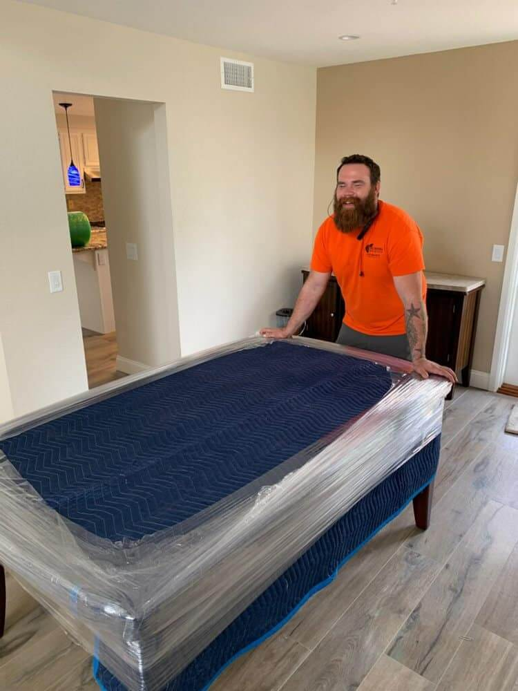 Mover carrying pool table for relocation