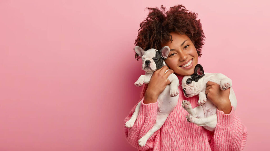 A girl in a pink sweater hugging two dogs